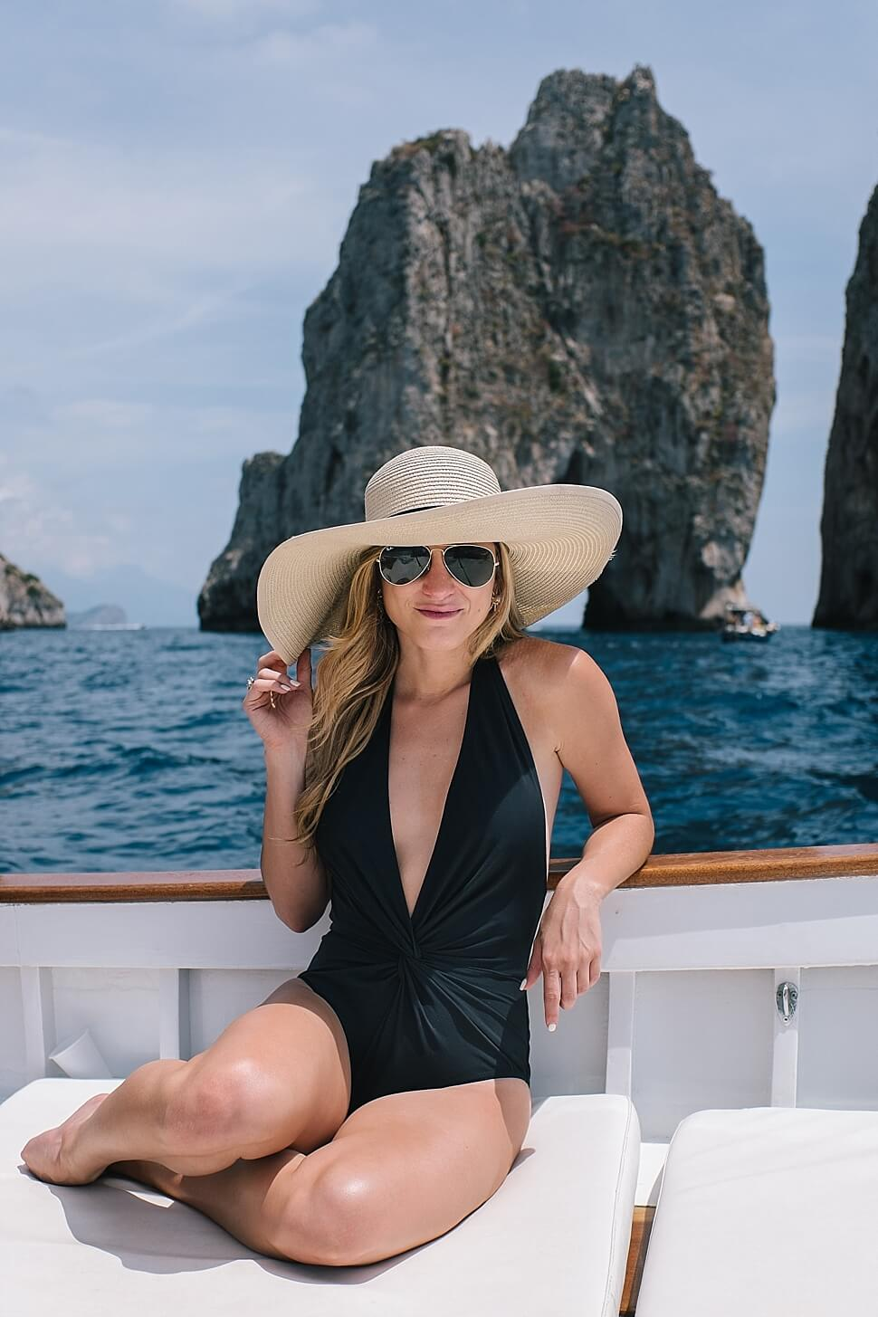 abb9adbc95689 brighton keller wearing black plunge front one piece on a private boat in capri  island italy
