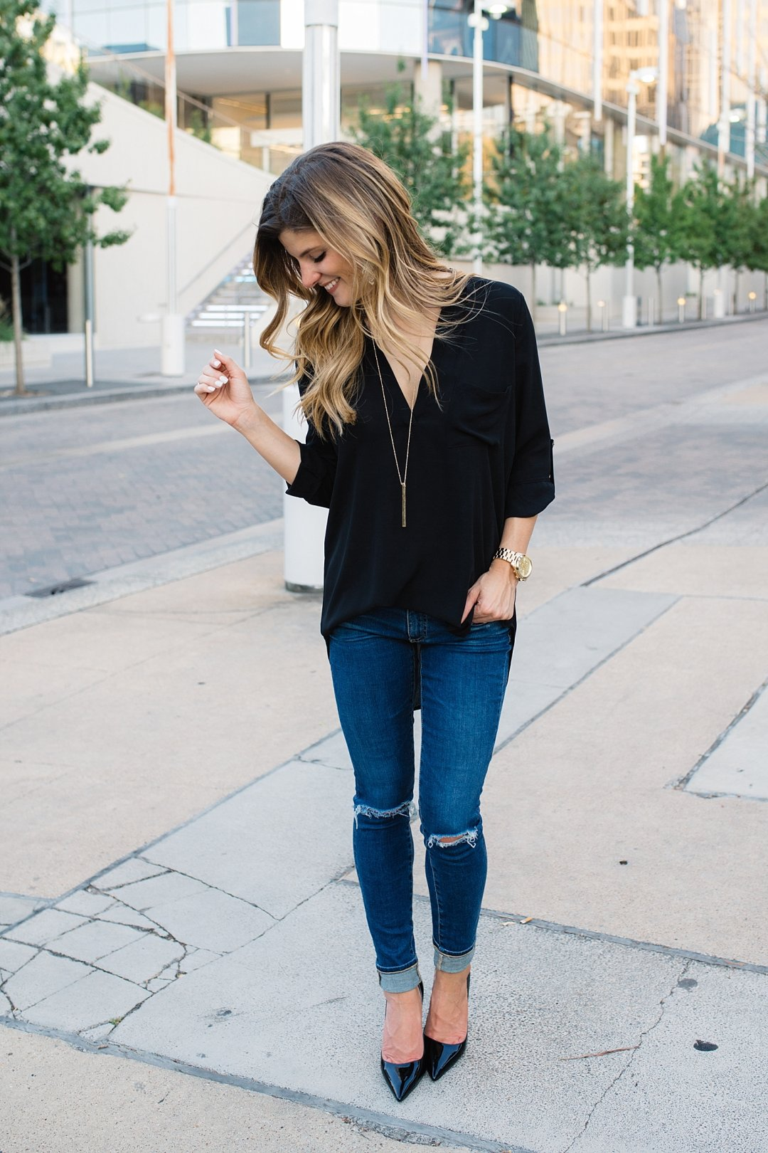 distressed denim + black top + gold necklace + pointy toe black pumps