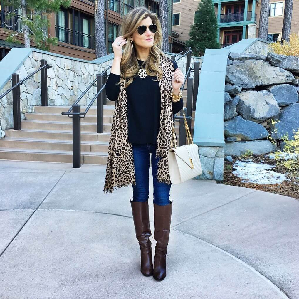 brighton keller wearing black sweater leopard scarf and riding boots