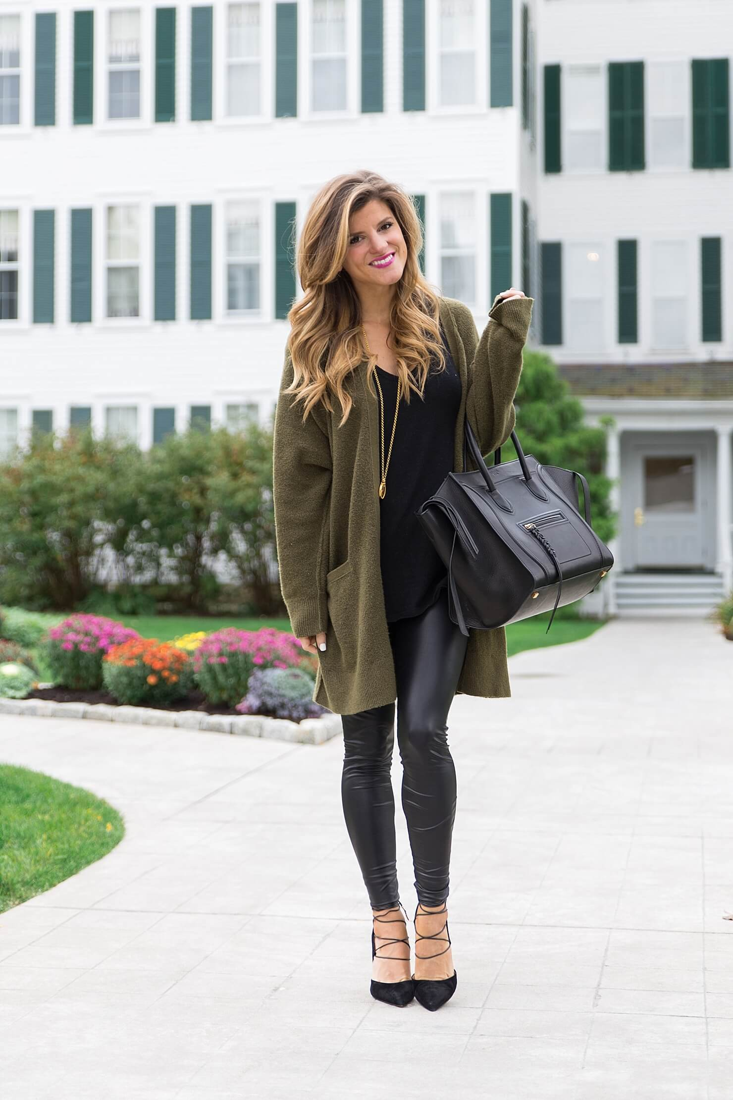 all black outfit idea, wearing all black with a long olive cardigan, liquid leather leggings winter outfit, black on black outfit, going out winter outfit, winter date night outfit, celine phantom tote, sam edelman strappy heels, winter all black outfit