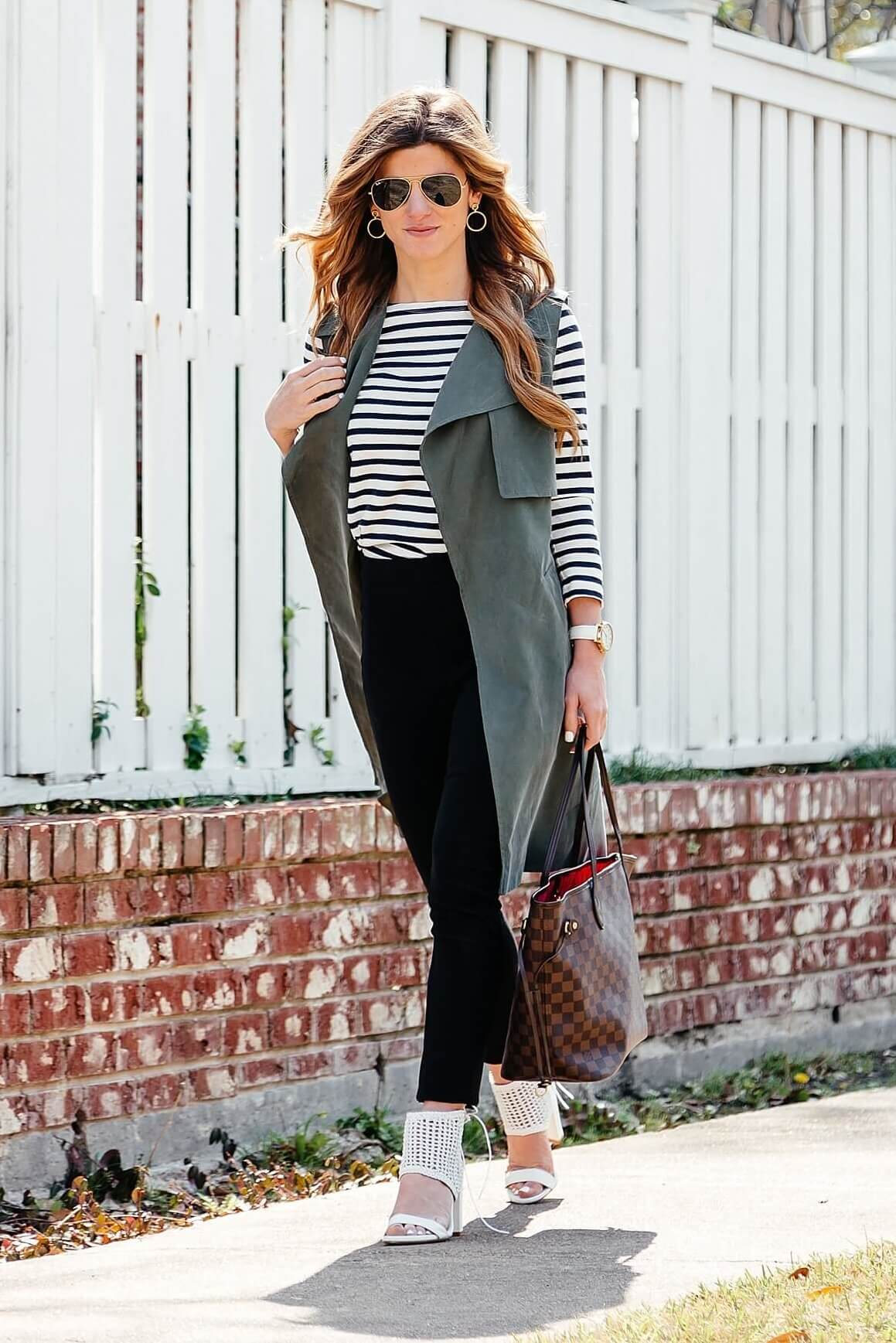 green trench vest, striped tee, black pants, business casual outfit idea