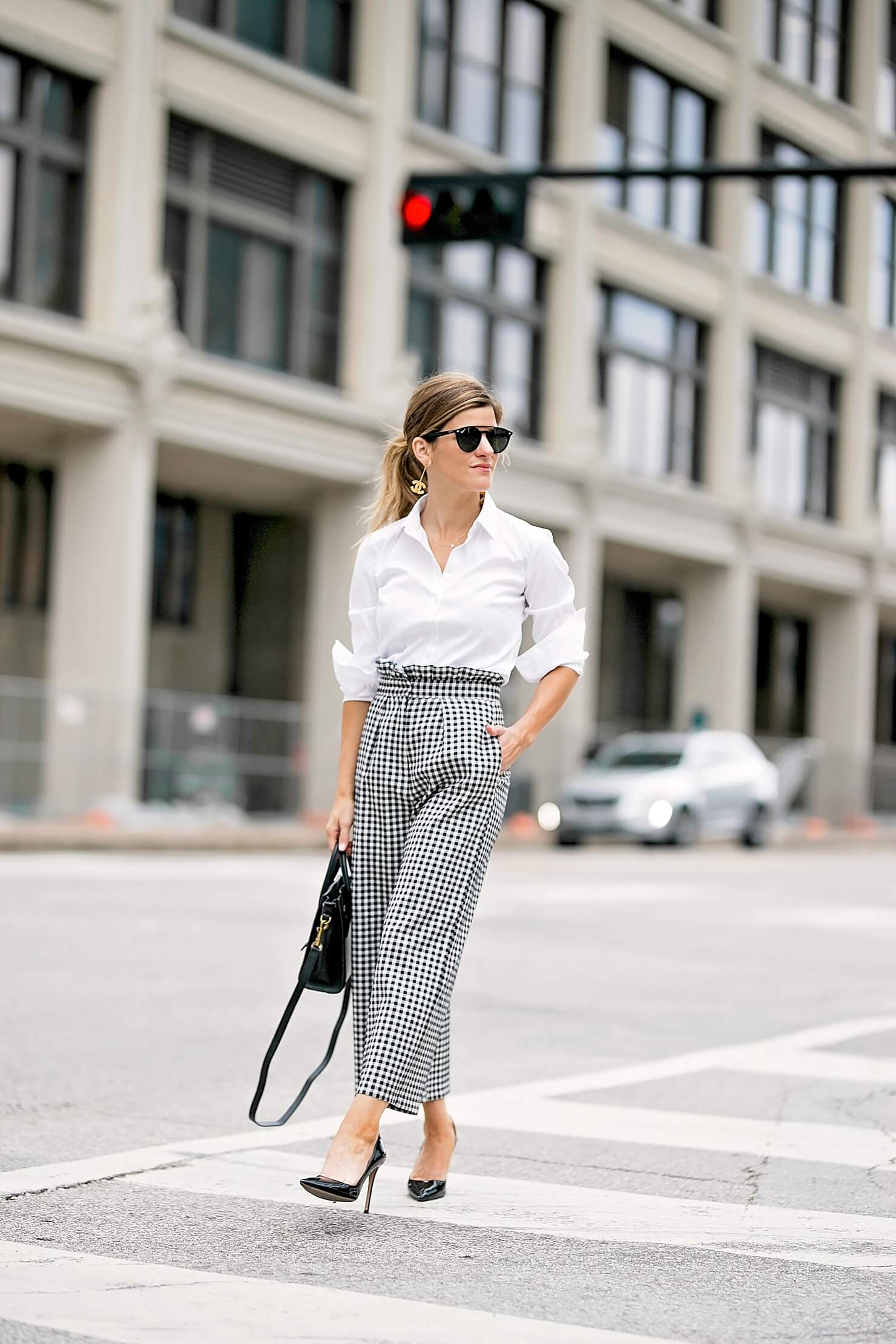 brighton keller wearing gingham pants with white button down and black pointy toe pumps