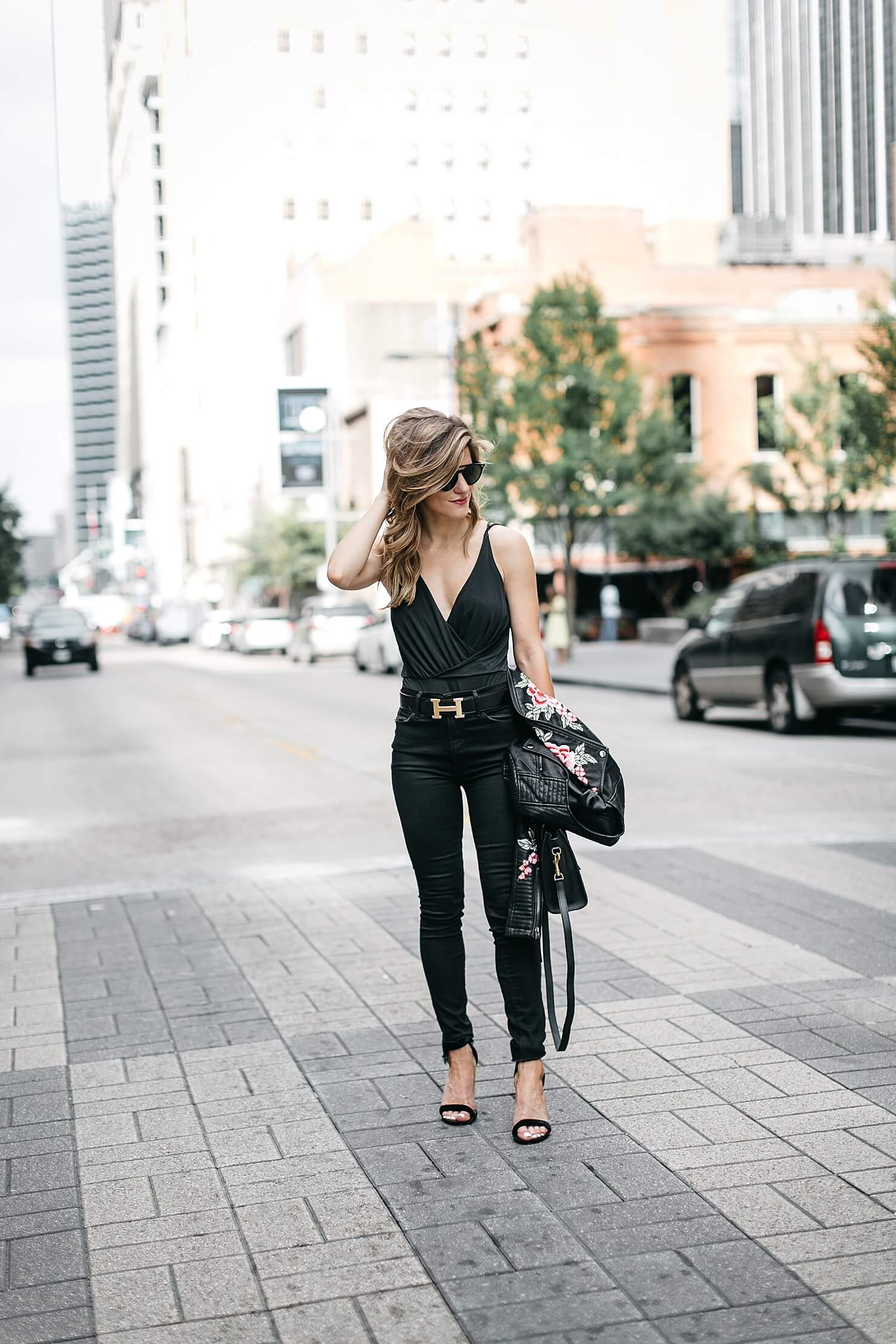 all black bodysuit outfit with embroidered leather jacket, black jeans, statement belt, and heels