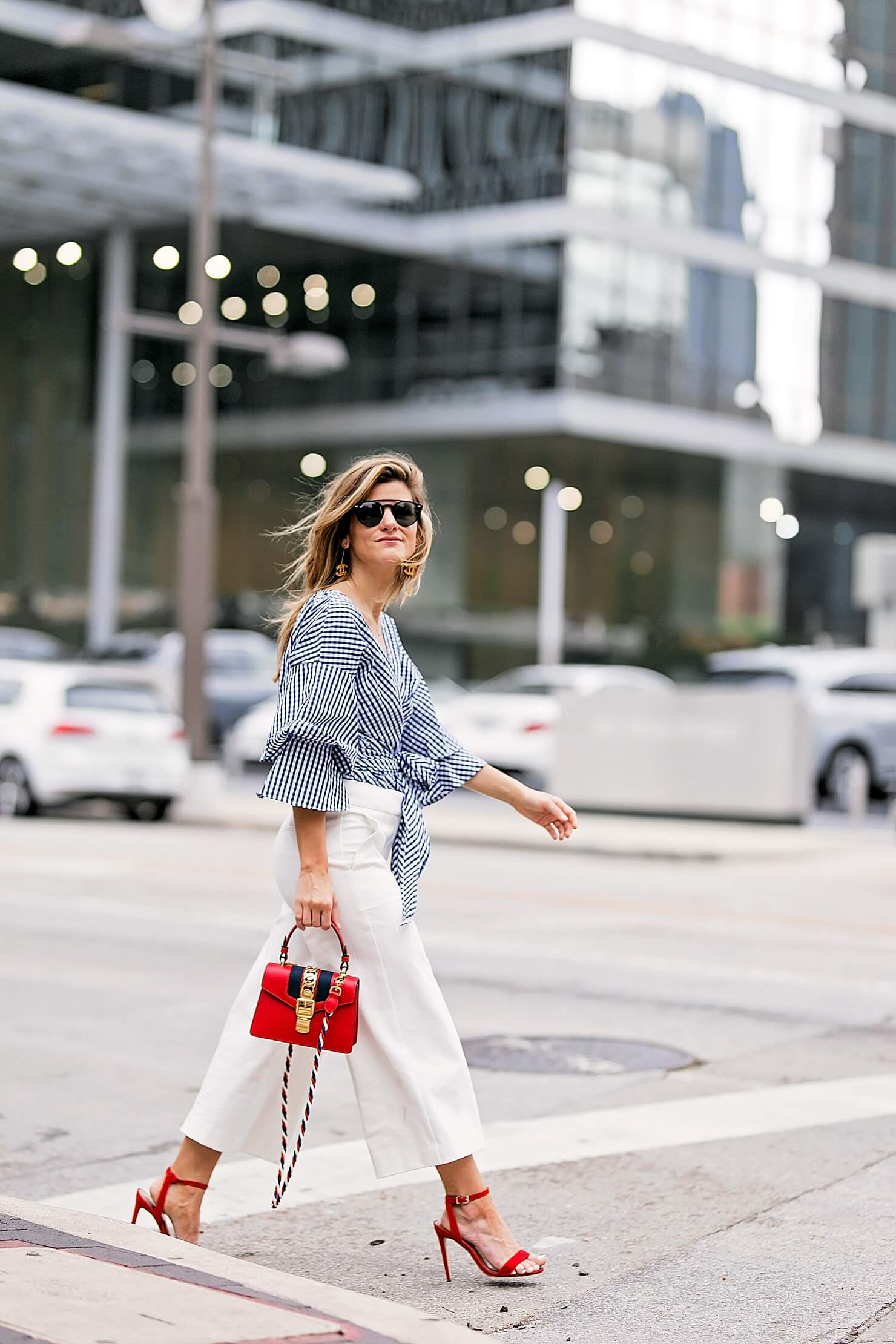 flared white pants with gingham wrap top, red heels and red bag