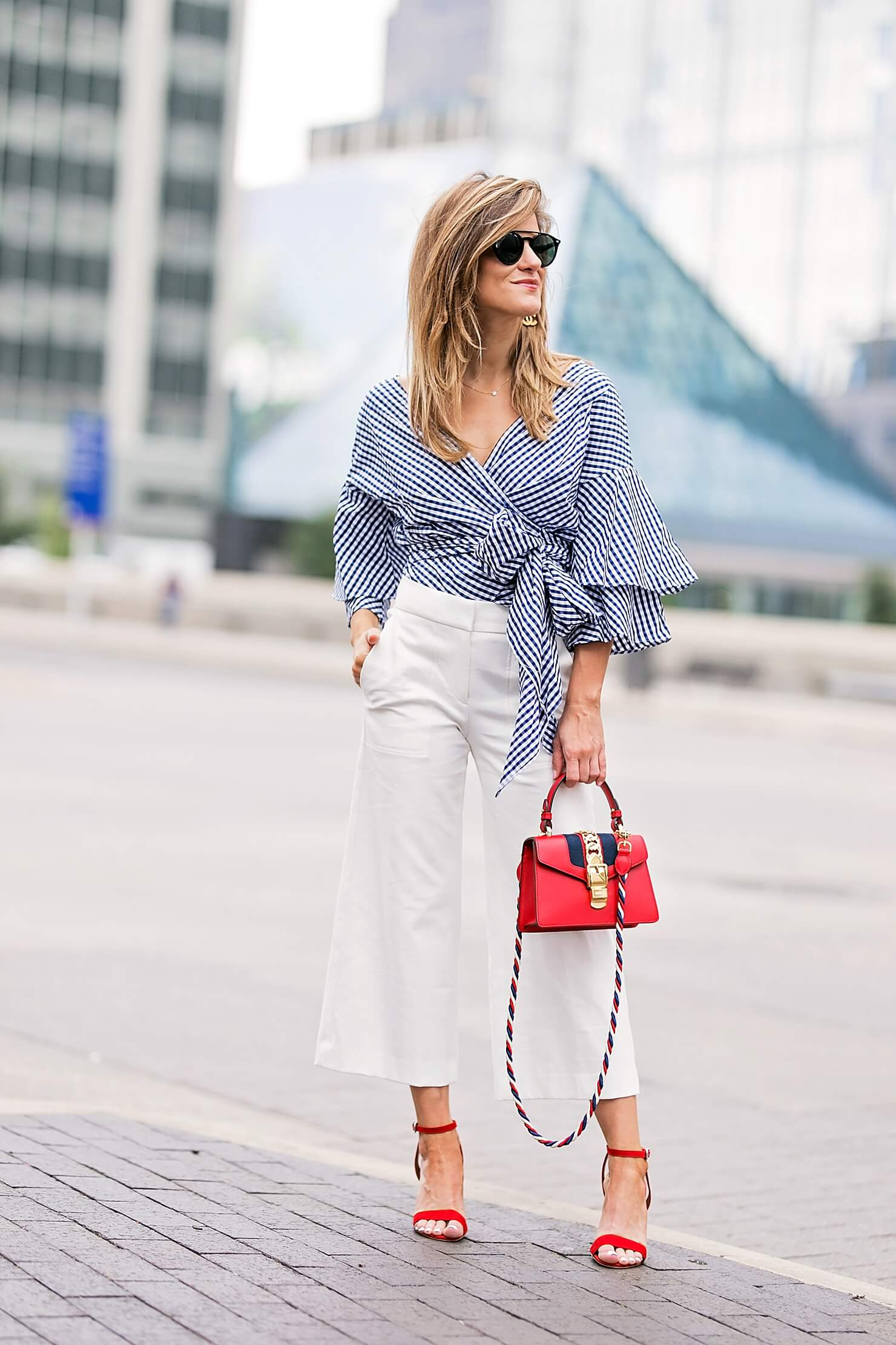 flared white pants with gingham wrap top, red heels and red bag, workwear