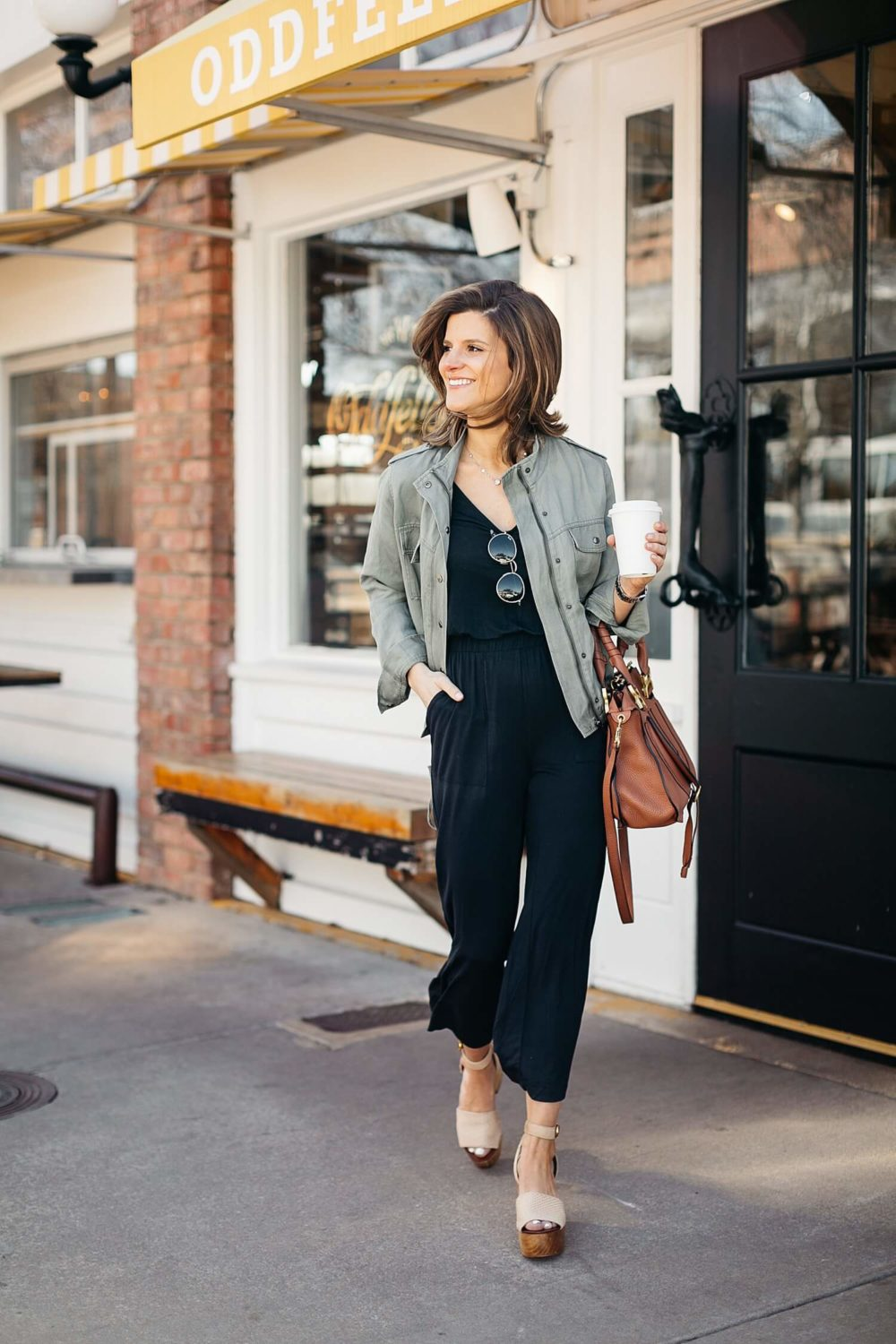 black jumpsuit paired with olive green utility jacket military jacket outfit