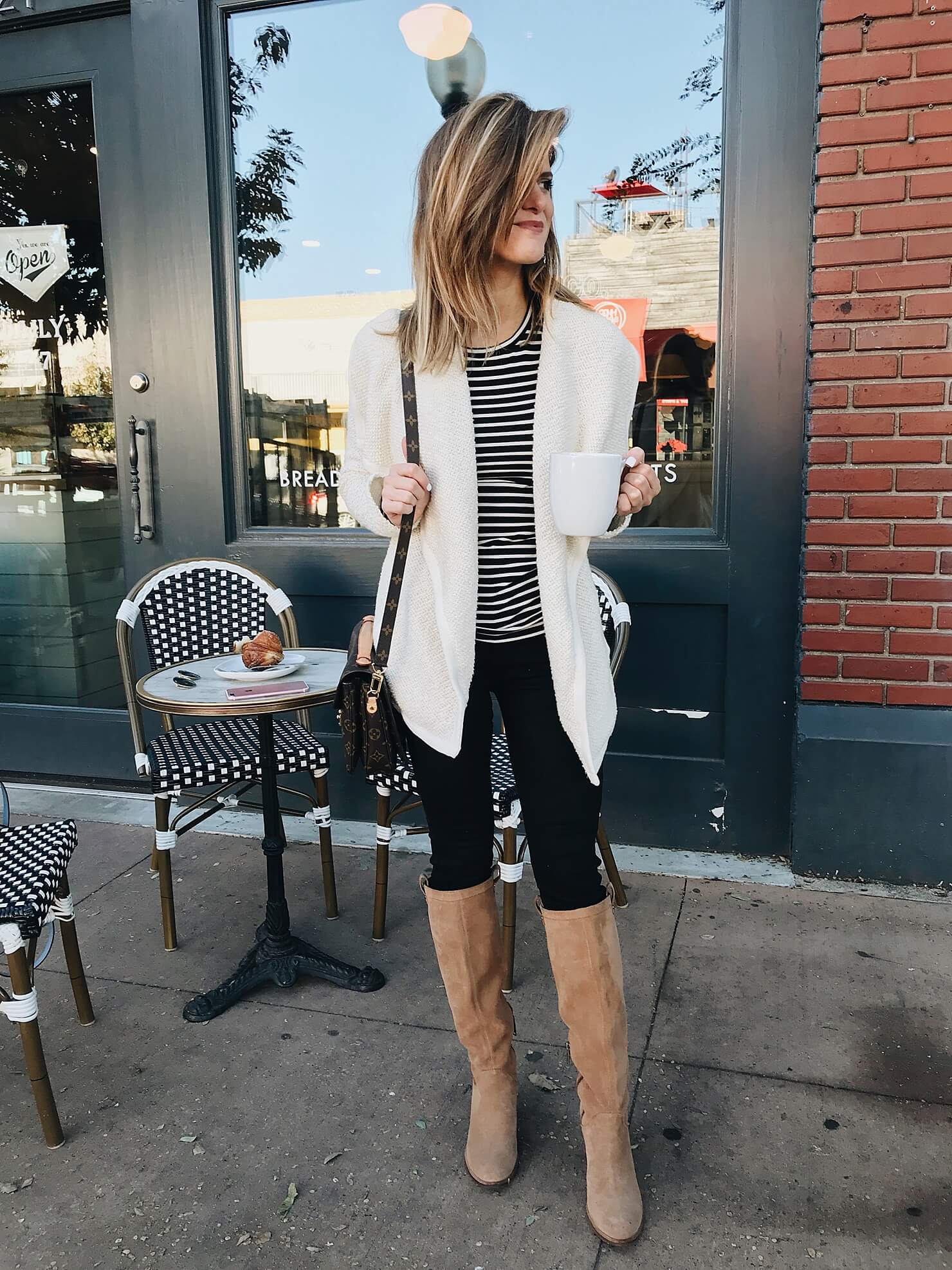 fall outfit idea with drape open front jacket, black and white stripe crewneck tee, black jeans, tall cognac suede boots