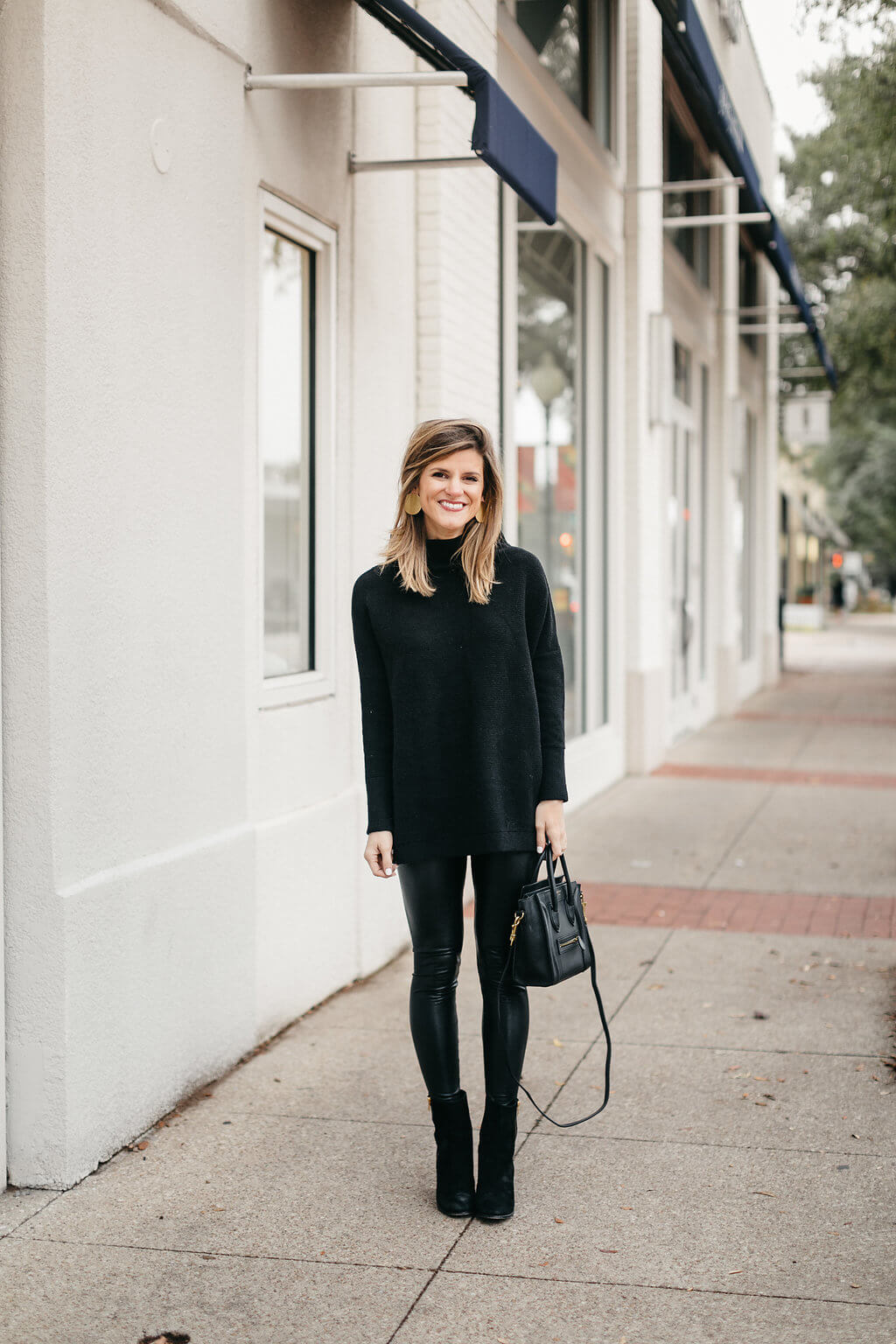 black tunic sweater, leather leggings, and black booties