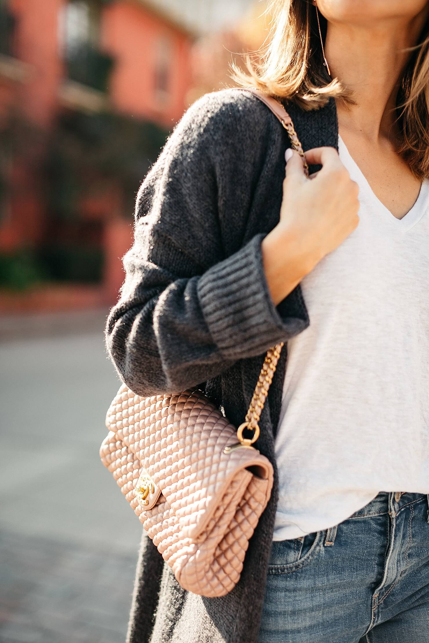 pink quilted Chanel bag with white tee and grey cardigan