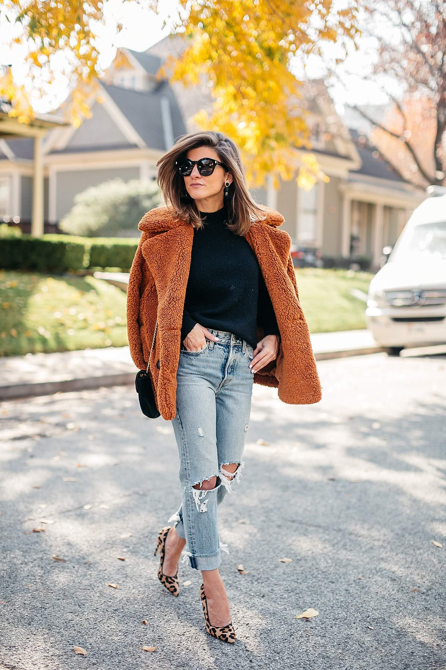 orange teddy coat, black sweater, distressed levi jeans, leopard pumps and gucci cross body