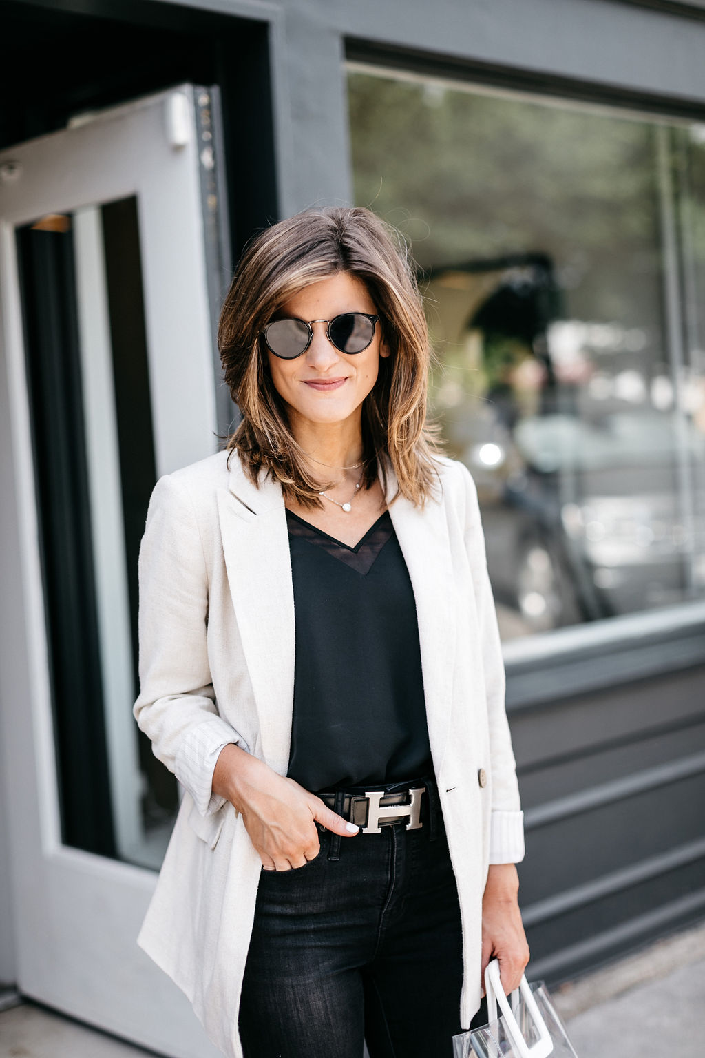 brighton keller wearing all black outfit with Hermes silver belt linen blazer