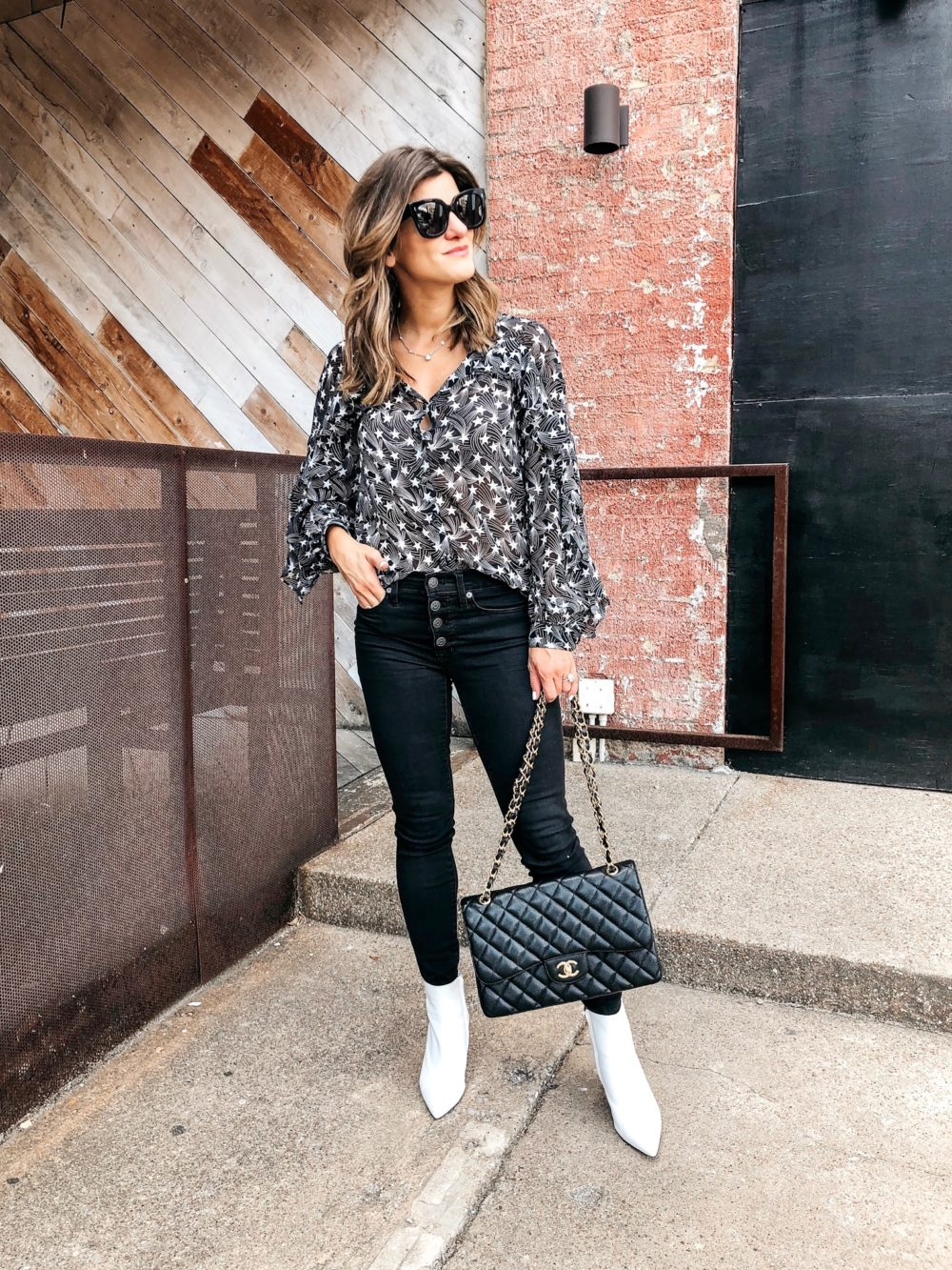 transitional fall outfit on brighton keller star print top with black jeans, white booties