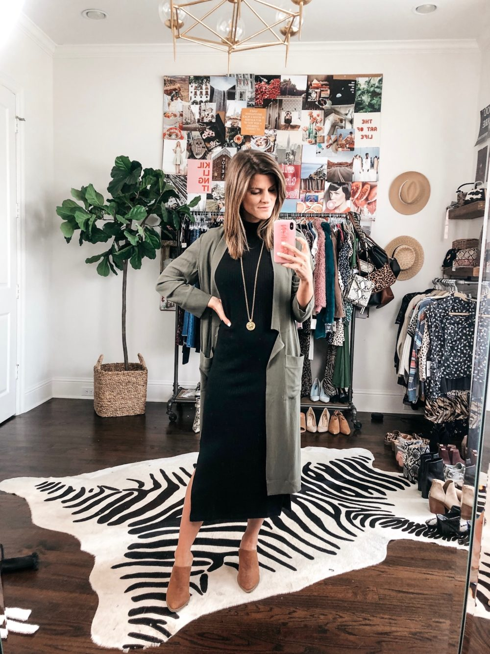 brighton keller wearing black midi dress with mules and olive green jacket and gold necklace