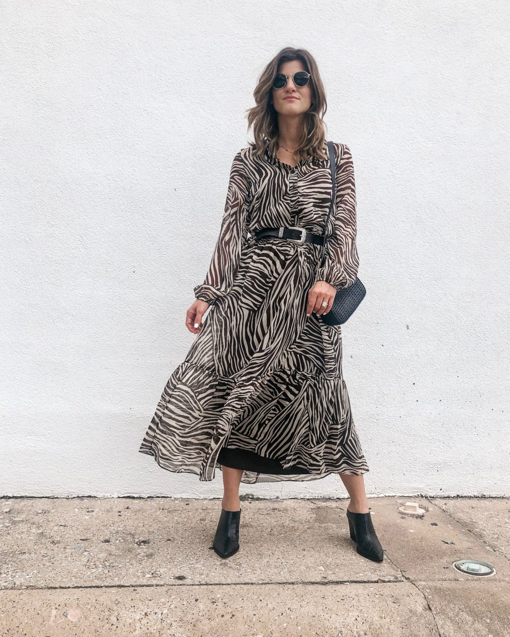brighton keller wearing animal print dress with mules and belt on white wall