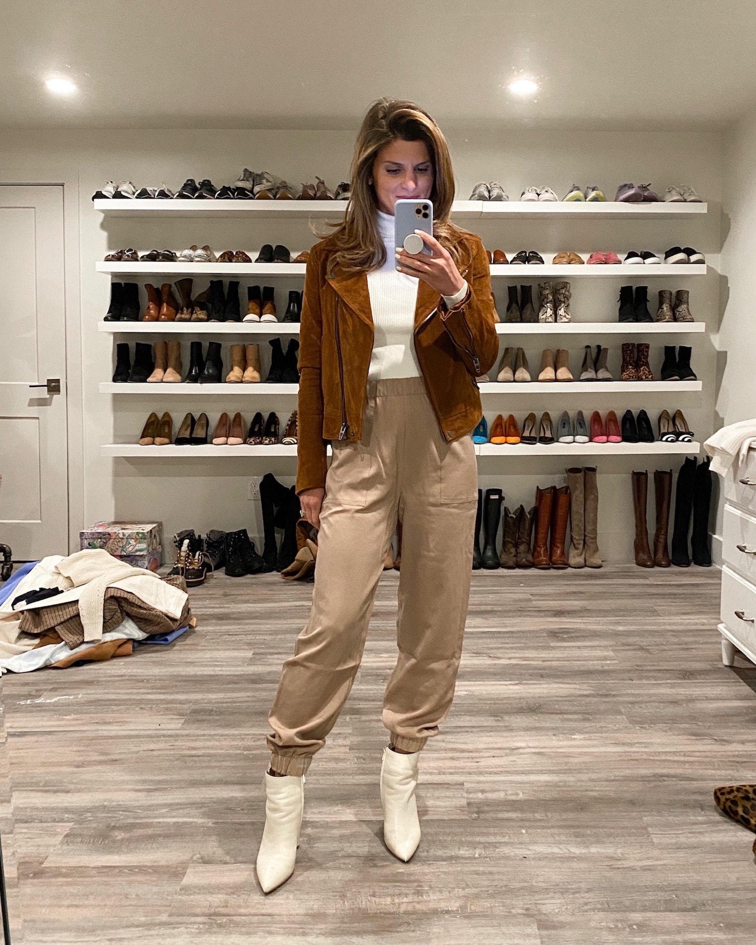 Brighton Keller wearing tan joggers, white turtleneck, suede jacket and white booties