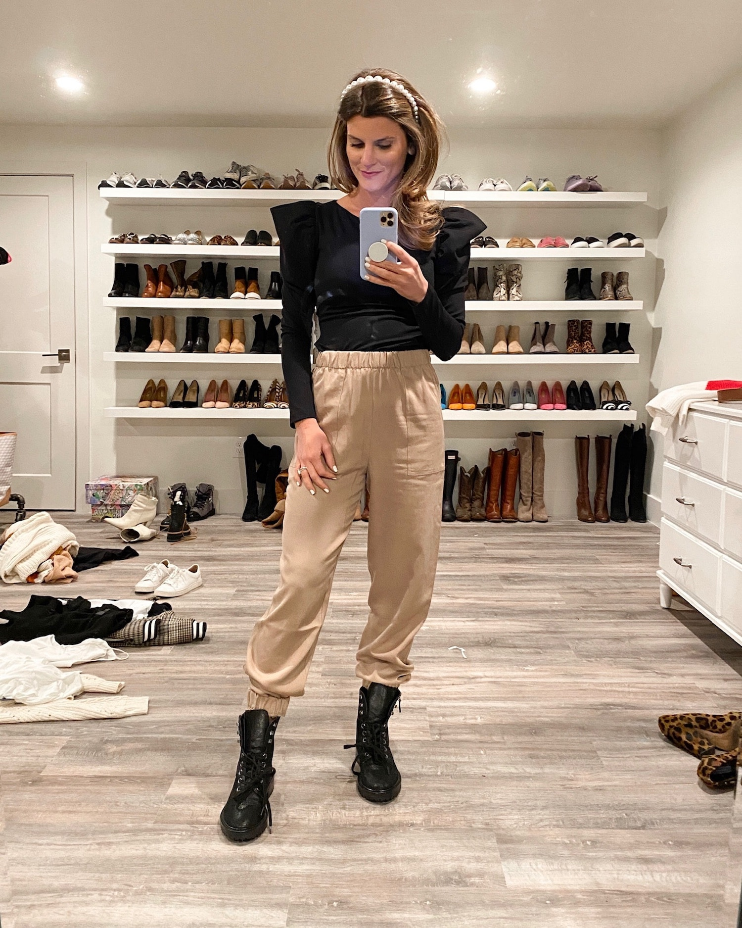 Brighton Keller wearing black puff sleeve sweater, tan joggers and combat boots