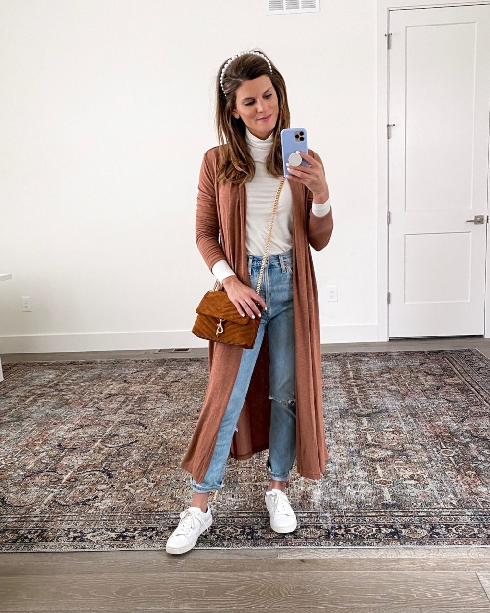 Brighton Keller wearing white turtleneck, rust duster, mom jeans and white sneakers