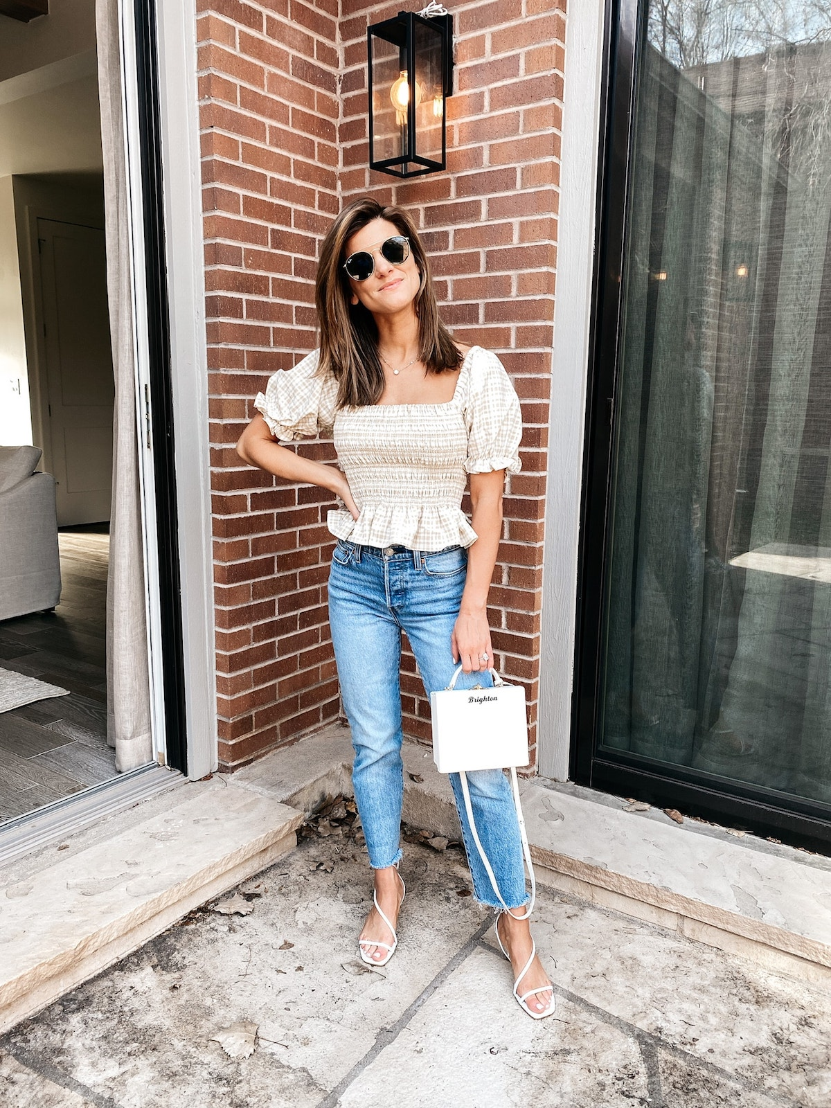 Brighton Keller wearing smocked tan top, Levi jeans, scrappy sandals and white purse