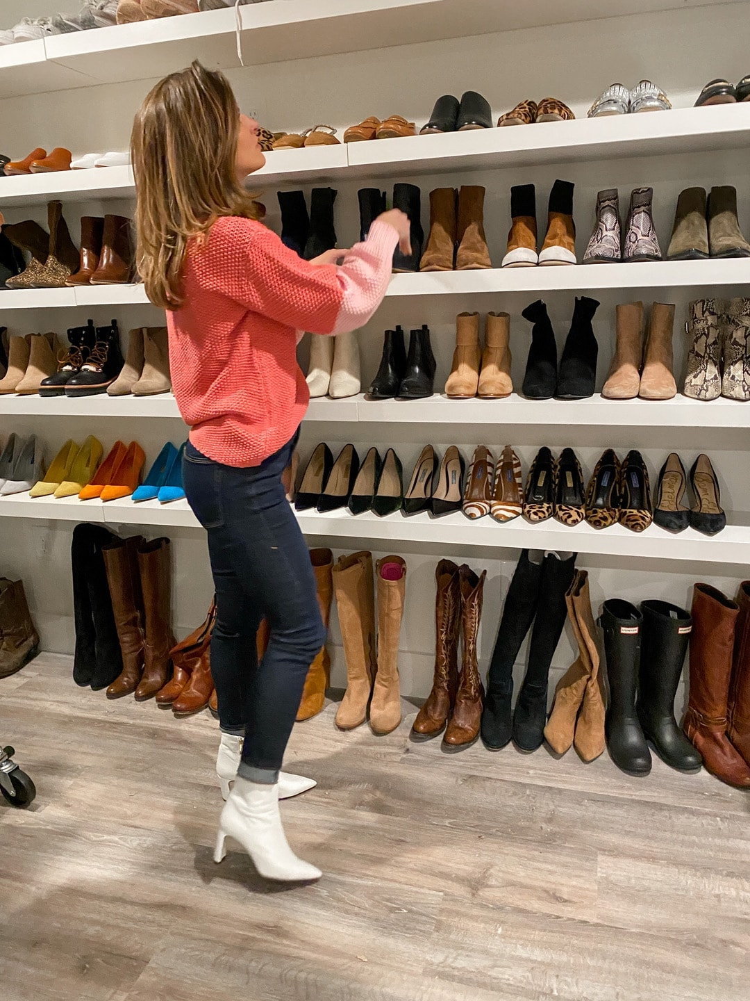Brighton Keller wearing pink sweater, white booties and dark wash jeans