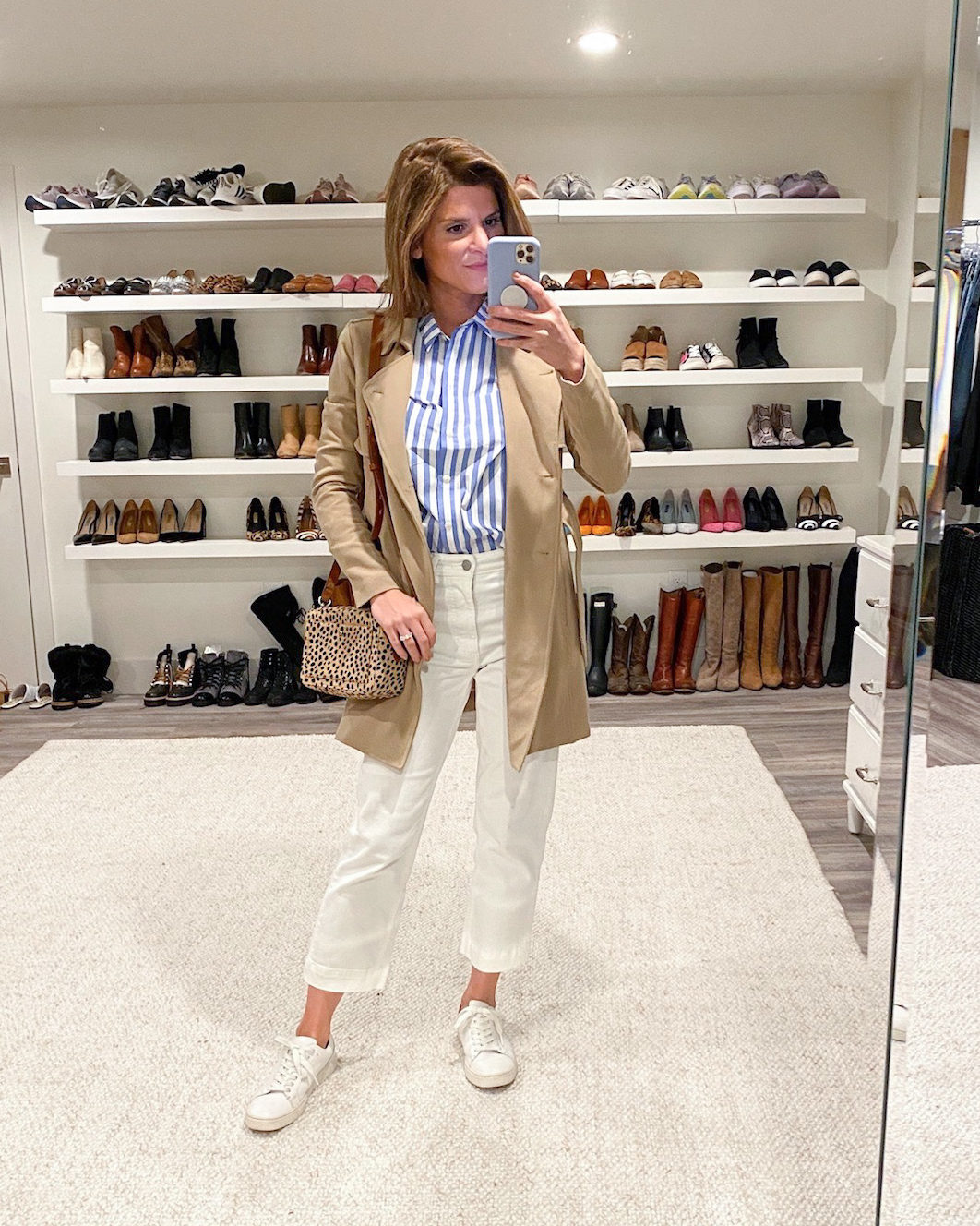 brighton butler wearing white wide leg pants, trench coat and white sneakers