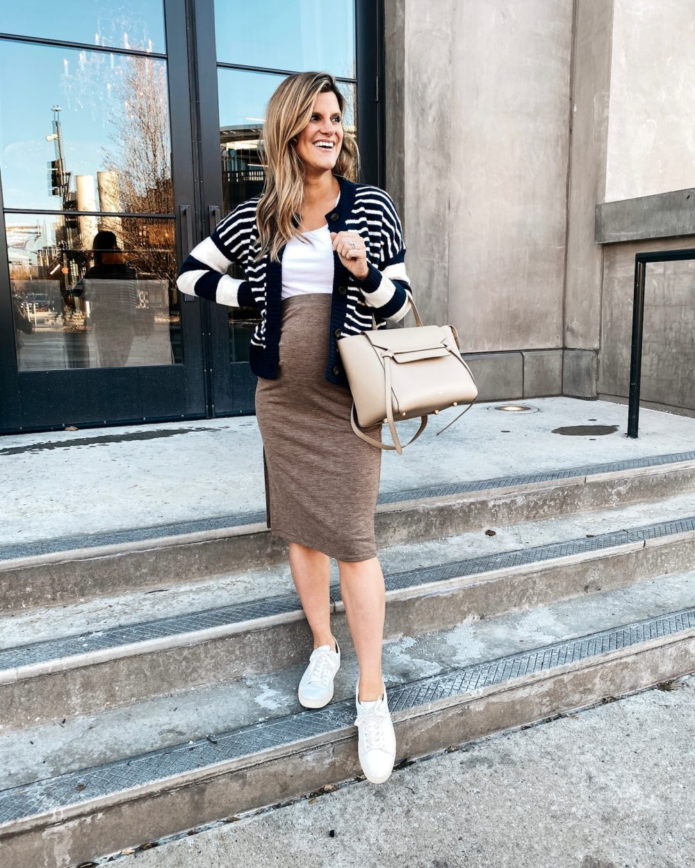 Brighton Butler wearing a tan sweater skirt, white tank, striped cardigan and sneakers, pregnancy style