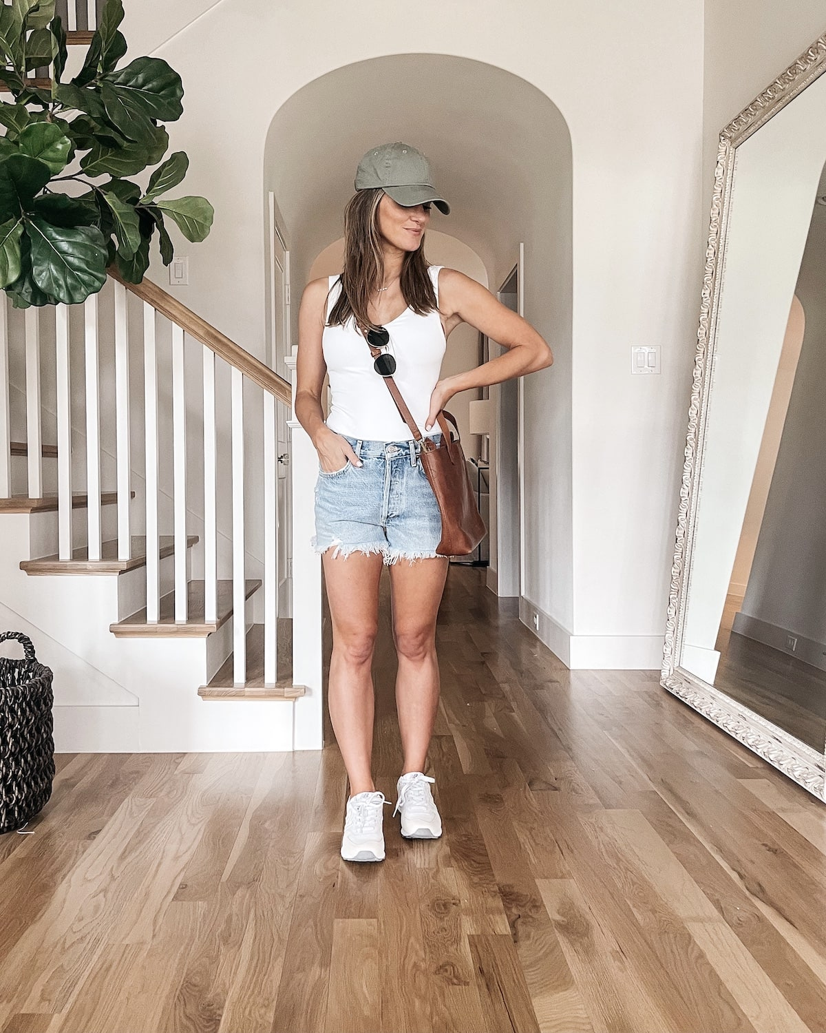 brighton butler wearing white body suit with jean shorts
