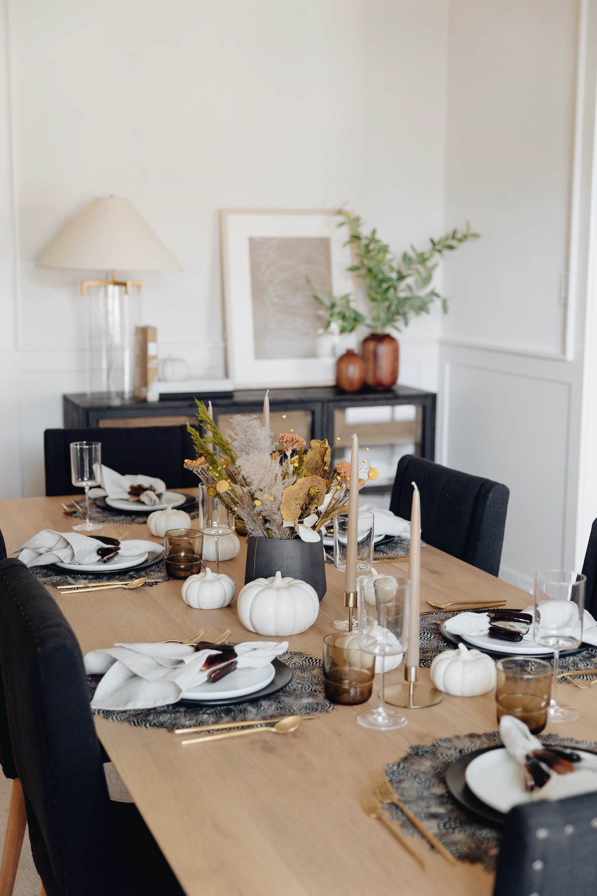Brighton Butler Fall table with black and white plates and feather placemat, dried flower arrangement