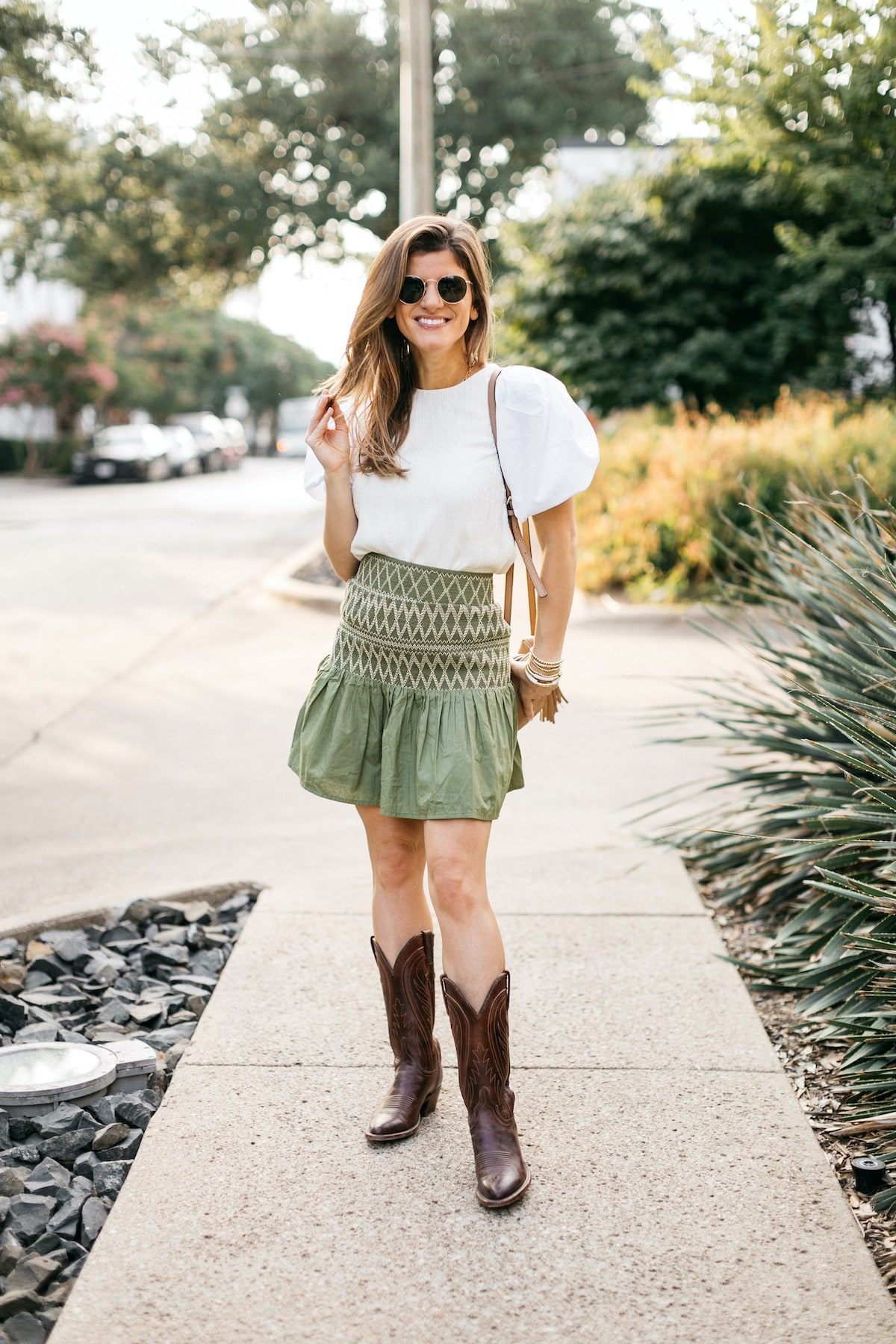 Brighton Butler wearing anthro green smocked shirt with white puff sleeved shirt and cowboy boots