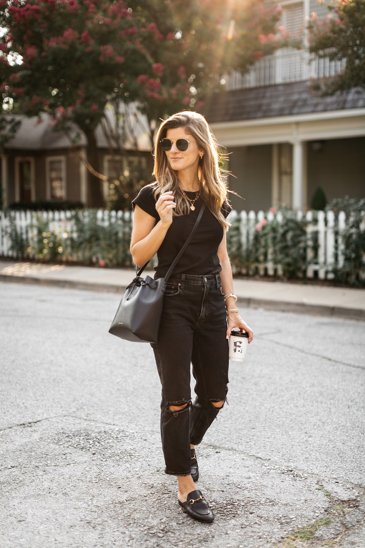 Brighton Butler wearing black tee with black jeans and black bucket bag