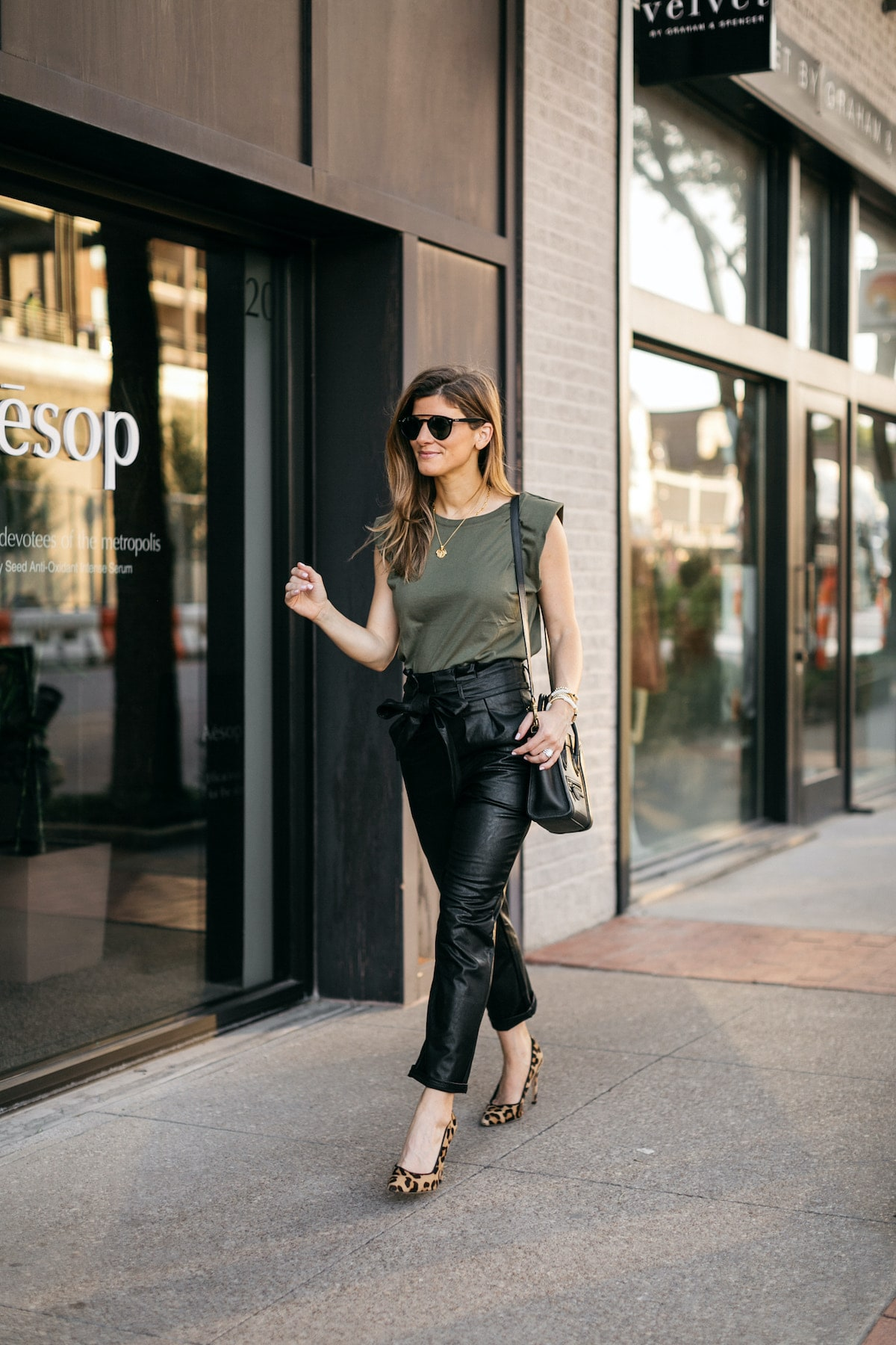 Brighton Butler wearing evereve leather pants with green padded tee and leopard heels
