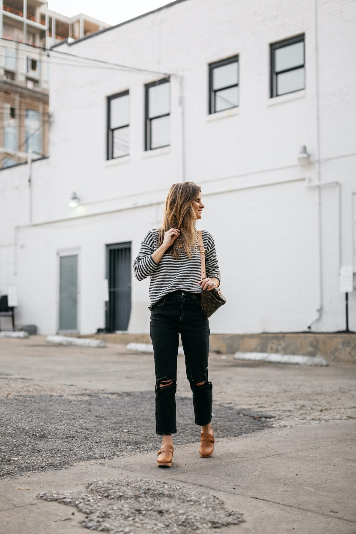 Brighton Butler wearing madewell clogs, striped sweater, black abercrombie jeans and bumbag