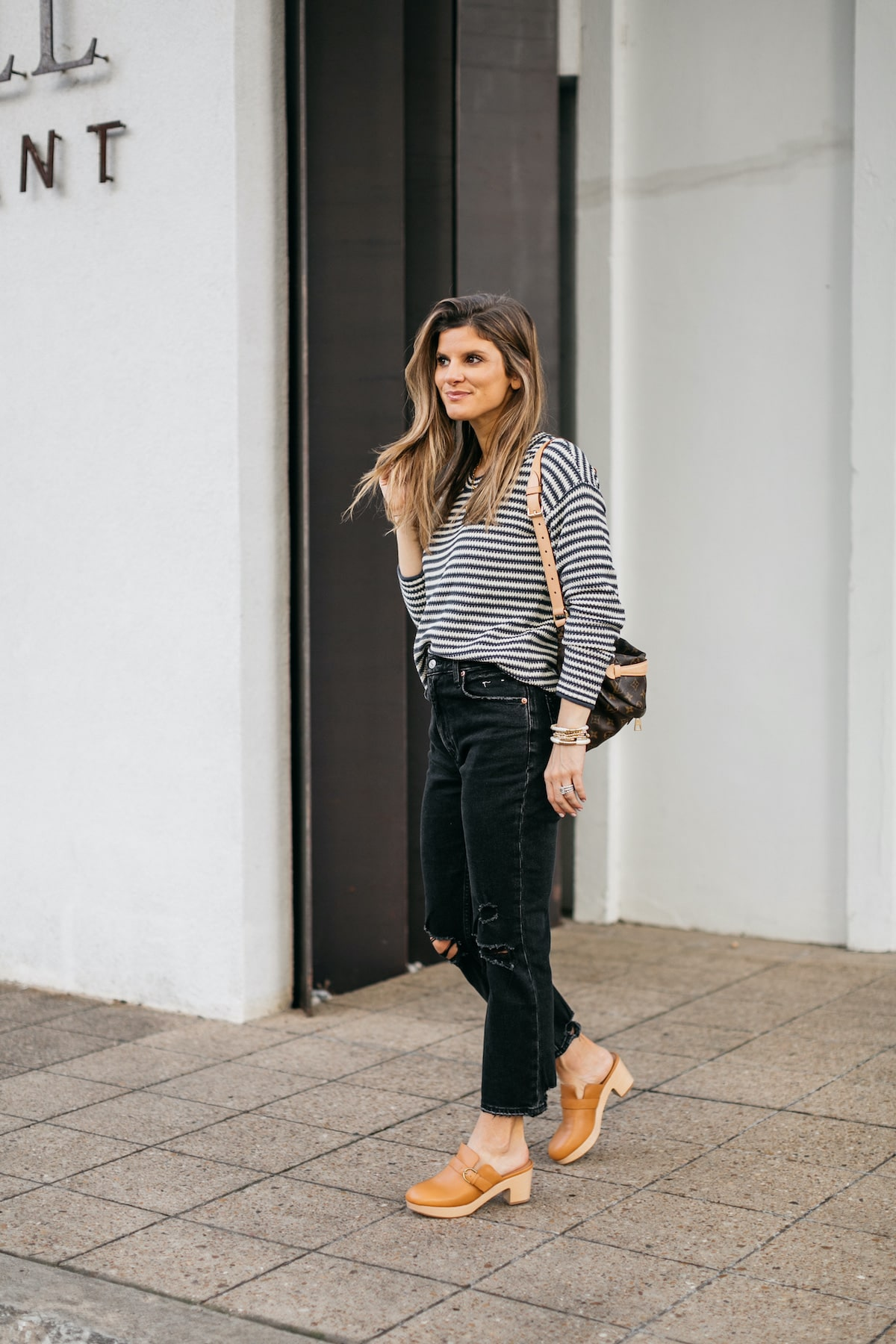 Brighton Butler wearing striped madewell sweater with black jeans, clogs and LV bumbag