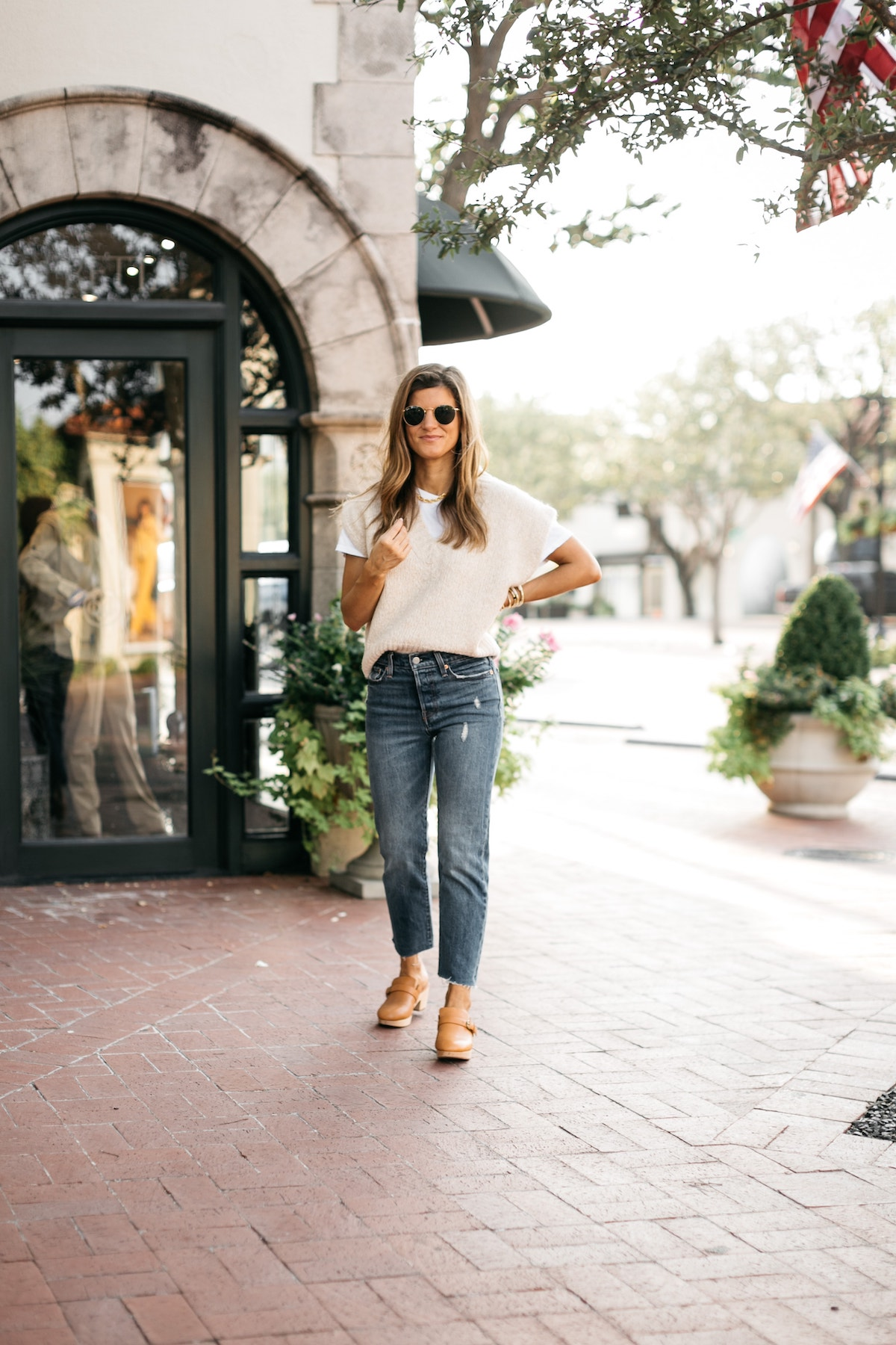 Brighton Butler wearing sweater vest layered over white tee, Levi's denim, clogs, sweater vest trend