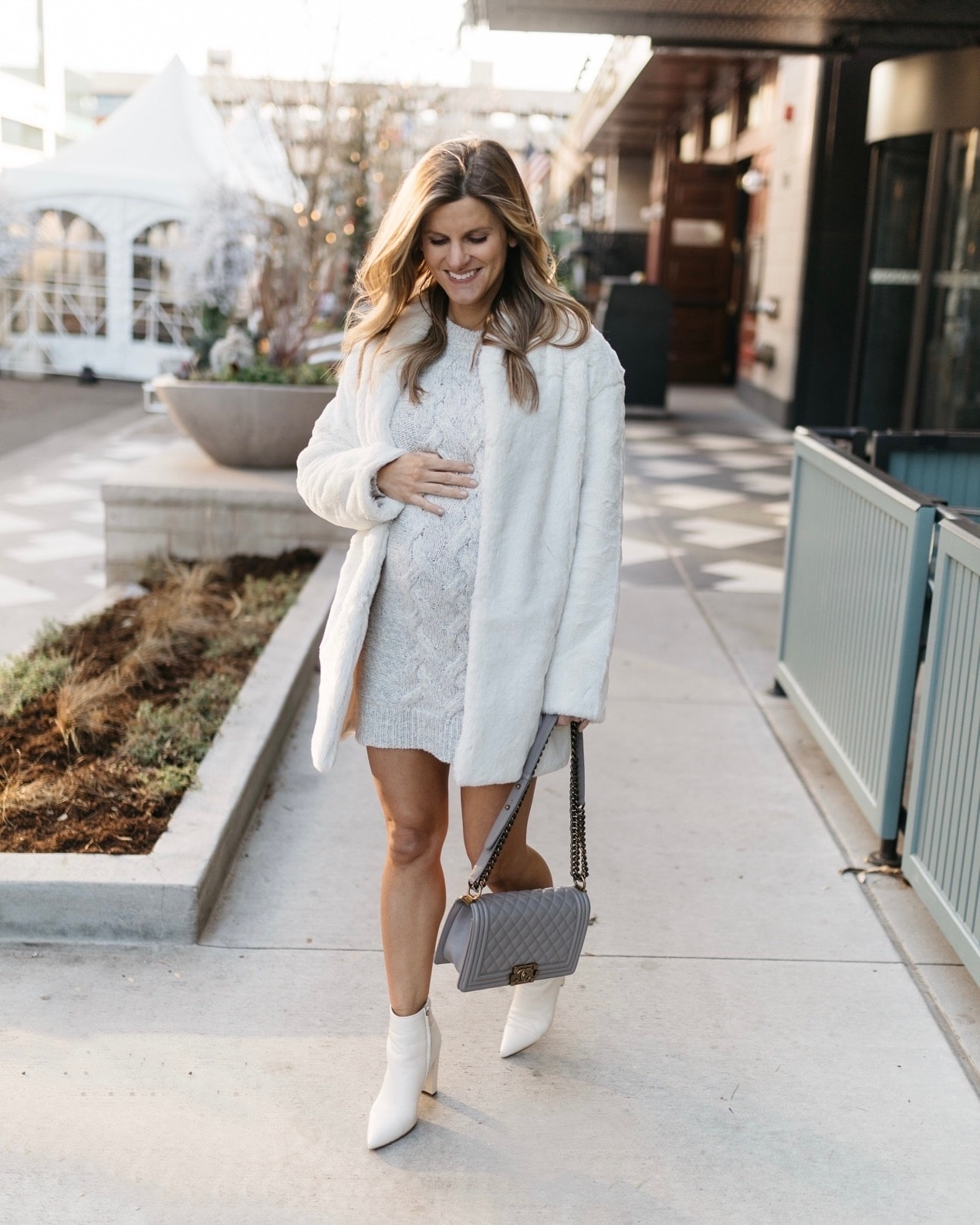 Brighton Butler in white fur jacket, grey sweater dress and white booties